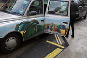 A black cab carrying door advertising for GWR rail travel, stops to drop-off a fare outside the Selfridges department store on Oxford Street, on 4th March 2019, in London England.