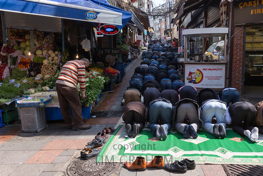 Muslims at Friday prayer on prayer mat by mosque at food and spice market Kadikoy district Asian side Istanbul, East Turkey