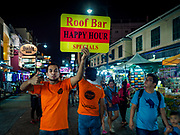 """24 JULY 2018 - BANGKOK, THAILAND:  A tout tries to get tourists to go into a bar on Khao San Road, in Bangkok. Khao San Road is Bangkok's original """"Backpacker Ghetto"""" and is still a popular hub for travelers, with an active night market and many street food stalls. The Bangkok municipal government plans to shut down the street market by early August because city officials say the venders, who set up on sidewalks and public streets, pose a threat to public safety and could impede emergency vehicles. It's the latest in a series of night markets the city has closed.    PHOTO BY JACK KURTZ"""