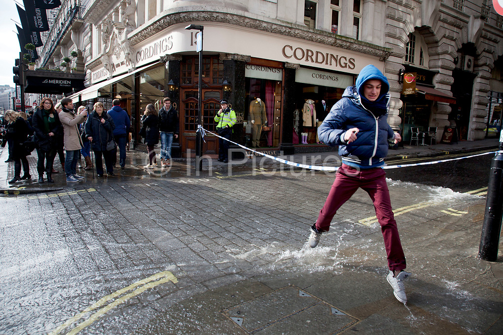 London, UK. Saturday 2nd March 2013. Burst water main causes flooding disruption in central London. People run through the flowing water running onto Piccadilly.