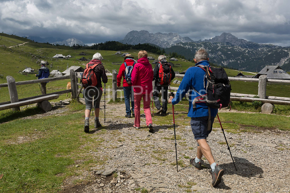 Walkers leave the chapel dedicated to Our Lady of the Snows, built in 1938 by the Slovenian architect Jože Plečnik, above the collection of Slovenian herders mountain huts in Velika Planina, on 26th June 2018, in Velika Planina, near Kamnik, Slovenia. Velika Planina is a mountain plateau in the Kamnik–Savinja Alps - a 5.8 square kilometres area 1,500 metres 4,900 feet above sea level. Otherwise known as The Big Pasture Plateau, Velika Planina is a winter skiing destination and hiking route in summer. The herders huts became popular in the early 1930s as holiday cabins known as bajtarstvo but these were were destroyed by the Germans during WW2 and rebuilt right afterwards by Vlasto Kopac in the summer of 1945.