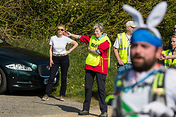Maidenhead, UK. 19th April, 2019. A man with rabbit ears runs past Prime Minister Theresa May as she serves as a marshal at the annual Maidenhead Easter 10 charity race on Good Friday.