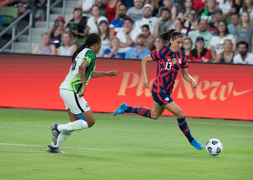 USA's Alex Morgan (13) drives past Onome Ebi as the US Women's National Team (USWNT) beats Nigeria, 2-0 in the inaugural match at Austin's new Q2 Stadium. The U.S. women's team, an Olympic favorite, is wrapping up a series of summer matches to prep for the Tokyo Games.