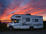 At sunset, lines of pink and magenta clouds glow in blue sky over a recreational vehicle (RV), in Ninilchik, Alaska, USA. Ninilchik is on the west side of the Kenai Peninsula, 38 miles southwest of Kenai on Sterling Highway, 188 miles by road from Anchorage and 44 miles from Homer. Ninilchik hosts the annual Kenai Peninsula State Fair. The Alaska Native Claims Settlement Act recognized Ninilchik as an Alaska Native village.