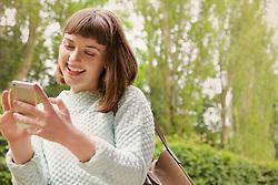 Teenage Girl Using Smartphone Outdoors, Smiling