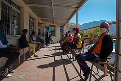 Patients waiting to be seen at De Doorns Clinic, a Western Cape government facility, in the Cape Winelands, where social-distancing rules are in effect, Wednesday May 6, 2020. The COVID-19 pandemic is a challenge, explains Abrey Arendse, Operational Manager here. Each morning, hundreds of patients line up outside the fenced clinic, according to social-distancing markers on the ground. She personally assesses everyone to see who needs to come inside the clinic right away, including the elderly, very sick, pregnant ladies and disabled people. Due to COVID-19, and space reasons, she can't let them all inside. There is also not enough PPE on hand for patients and no long-term stock for staff. Meanwhile, it's difficult to leave patients waiting in the elements outside. The sun is strong, and the winter rains are coming. PHOTO: EVA-LOTTA JANSSON