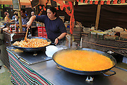 Woman cooking local food in giant pans on a market stall, Algeciras, Spain