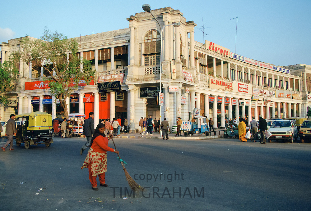 Woman street cleaner at work in shopping district of Connaught Place in New Delhi, India