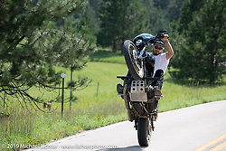 Hooligan racer Ethan White wheelying down the road during the Sturgis Black Hills Motorcycle Rally. SD, USA. Friday, August 9, 2019. Photography ©2019 Michael Lichter.