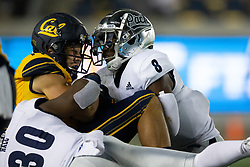 California wide receiver Monroe Young (14) is brought down by Nevada defenders Lawson Hall (30) and JoJuan Claiborne (8) during the third quarter of an NCAA college football game, Saturday, Sept. 4, 2021, in Berkeley, Calif. (AP Photo/D. Ross Cameron)