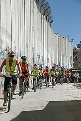 Cyclists on a charity bike ride near the wall of separation in Bethlehem. From a series of photos commissioned by  British NGO, Medical Aid for Palestinians (MAP).