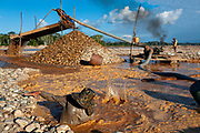 A miner removes the stones that clog a hose that sucks the mud, a motor drives the mud so that it collides with a mesh and it slid along a carpet and by gravity the gold is trapped. Bed of the Madre de Dios River near Boca Colorado, Peru.