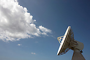 A VT Merlin satellite tracking dish appears to blow clouds across a blue sky at the Diane Tracking station, French Guiana