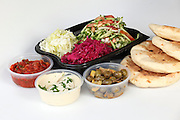 Pita and Middle Eastern salds in disposible plastic containers (front row left to right Spicy Turkish salad, Tahini and olives)