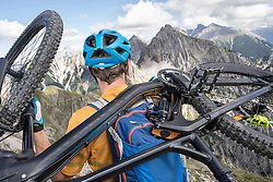 Rear view of a mountain biker carries his bike on shoulder and walking uphill, Tirol, Austria