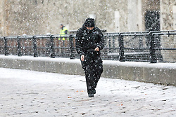 © Licensed to London News Pictures. 10/12/2017. London, UK. A man walks past the Tower of London during heavy snow fall. Heavy snow has fallen across the UK this morning. Photo credit: Vickie Flores/LNP