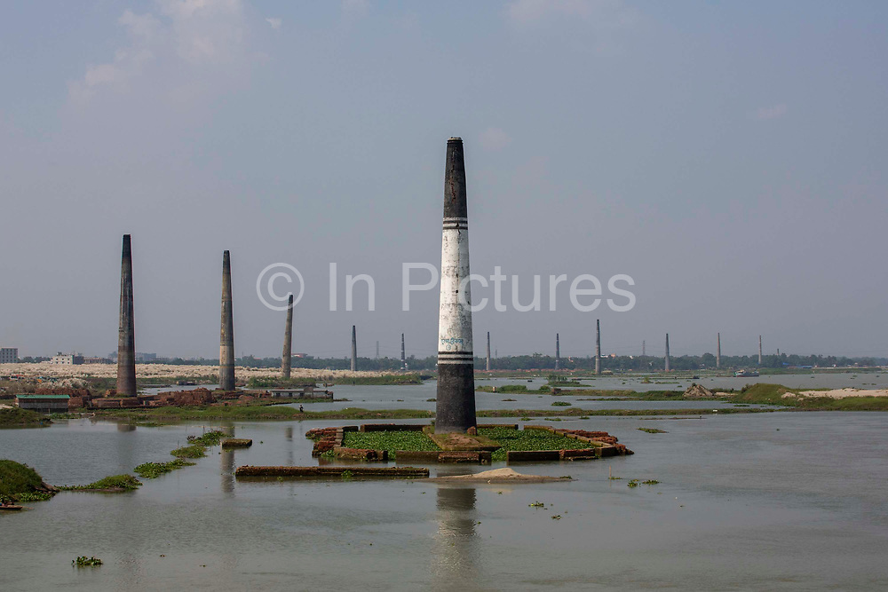 Chimney stacks of brickfields in the flood plains of the Turag river on the 1st of October 2018  in the Ashulia district of Dhaka, Bangladesh.