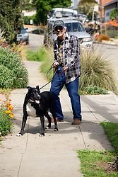 Jack Boise, 79, walks his dog along Coolidge Avenue on Monday, March 30, 2020 in Oakland, Calif. The entire Bay Area is under a mandatory shelter-in-place order in an effort to slow the spread of the novel coronavirus dubbed COVID-19. (Photo by D. Ross Cameron)