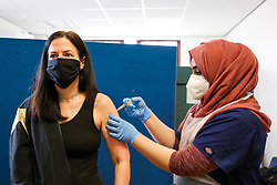 © Licensed to London News Pictures. 21/03/2021. London, UK. A NHS staff member administers the Oxford AstraZeneca Covid-19 vaccine to a woman at Masjid Ayesha, a mosque in Tottenham, north London. The mosque is working in partnership with Federated4Health and is encouraging local communities to be inoculated. The government announced that over 26 million people have now received a first dose of a vaccine and over 2 million have received their second dose of a vaccine. Prime Minister Boris Johnson received his first dose on Friday. <br /> <br /> ***Permission Granted***<br /> <br /> Photo credit: Dinendra Haria/LNP