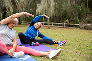 A group of senior women stretching on yoga mats outside