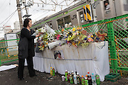 People leave flowers and pray at a level crossing near the JR Nakayama Station where Natsue Murada died, Kanagawa, Japan. Monday October 7th 2013. Natsue Murada (40) died trying to save a 74 year old man who had crossed the barriers and was lying on the tracks in the path of an on-coming train