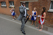 A smartly-dressed gentleman walks past betting promo girls during the annual Royal Ascot horseracing festival in Berkshire, England. Royal Ascot is one of Europe's most famous race meetings, and dates back to 1711. Queen Elizabeth and various members of the British Royal Family attend. Held every June, it's one of the main dates on the English sporting calendar and summer social season. Over 300,000 people make the annual visit to Berkshire during Royal Ascot week, making this Europe's best-attended race meeting with over £3m prize money to be won.