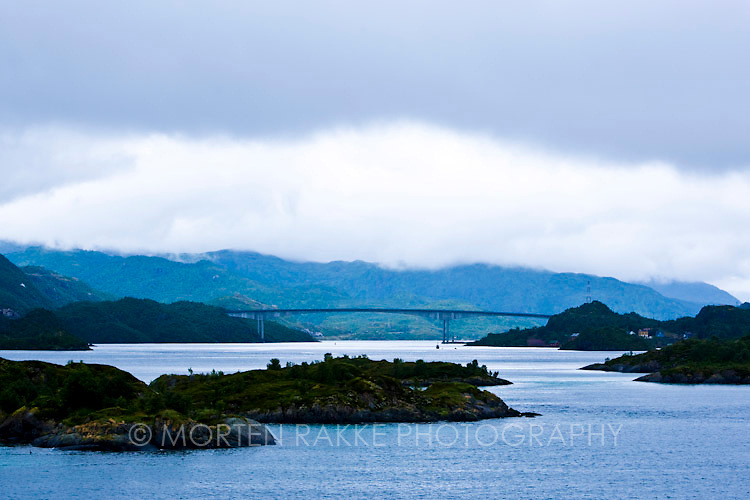 Norway, bridge over river with mountains in background