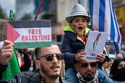 "© Licensed to London News Pictures. 16/05/2021. Oxford, UK. A young boy holding a ""Free Palestine"" placard sits on a mans shoulders at the 'Speak up for Palestine' demonstration held in Oxford, the crowd marched on the planned route from Manzil Way to Bonn Square in central Oxford. Photo credit: Peter Manning/LNP"