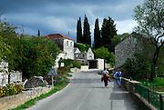 Two women walking through streets of village of Zrnovo, island of Korcula, Croatia