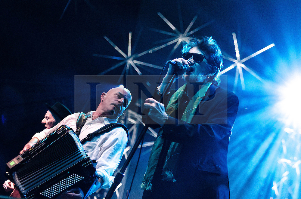 © Licensed to London News Pictures. 20/12/2012. London, UK.  James Fearnley (left) and Shane MacGowan (right) of The Pogues performing live at The O2 Arena for their only UK live date of 2012 as part of their 30th Anniversary Tour.  The Pogues are a Celtic punk band from London, formed in 1982 and fronted by Shane MacGowan.  Members include Shane MacGowan (vocals, guitar, banjo, bodhrán),.Spider Stacy (vocals, tin whistle), Jem Finer (banjo, mandola, saxophone, hurdy-gurdy, guitar, vocals), Andrew Ranken (drums, percussion, harmonica, vocals), .James Fearnley (accordion, mandolin, piano, guitar), .Philip Chevron (guitar, vocals),  Darryl Hunt (bass guitar),.Terry Woods (mandolin, cittern, concertina, guitar, vocals).     Photo credit : Richard Isaac/LNP