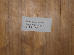 sign posted on a paneling wall