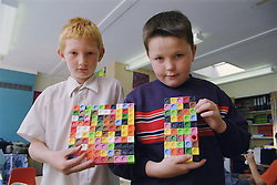 Primary school boys holding unilink blocks in practical maths lesson,
