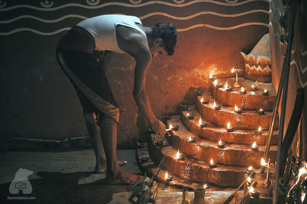 A kalaripayattu martial arts fighter lights rows of deepam (votive lights) on the training grounds' altar, Kumily, Kerala, India.