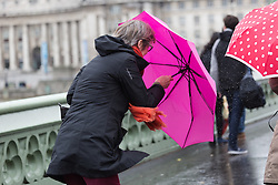 © Licensed to London News Pictures. 14/05/2015. London, UK. A woman struggles to control her umbrella during heavy rain and wet and windy weather in Westminster, central London today. Photo credit : Vickie Flores/LNP