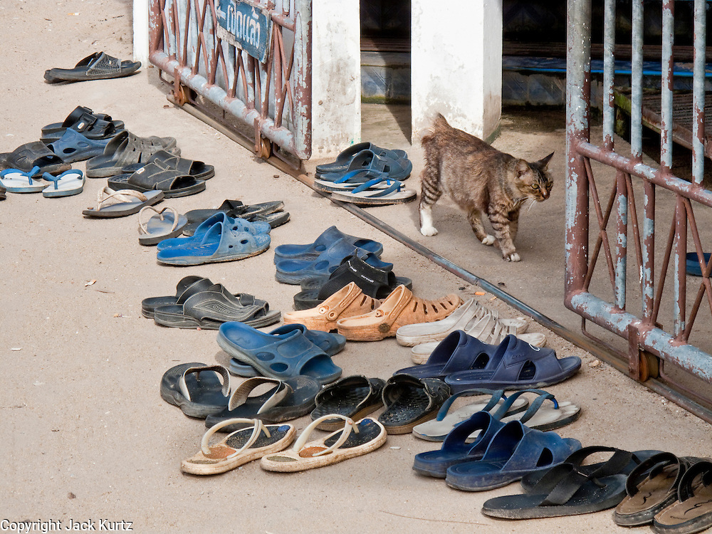 "Sept. 28, 2009 -- TANJONG DATO, THAILAND: Men's shoes lined up in front of the mosque in the Muslim village of Tanjong Dato, in the province of Pattani, Thailand. Everybody in the village is Muslim and they say they have no problems, but the roads around the village leading to the provincial capital of Pattani are too dangerous for them to use once it gets dark. Thailand's three southern most provinces; Yala, Pattani and Narathiwat are often called ""restive"" and a decades long Muslim insurgency has gained traction recently. Nearly 4,000 people have been killed since 2004. The three southern provinces are under emergency control and there are more than 60,000 Thai military, police and paramilitary militia forces trying to keep the peace battling insurgents who favor car bombs and assassination.   Photo by Jack Kurtz / ZUMA Press"