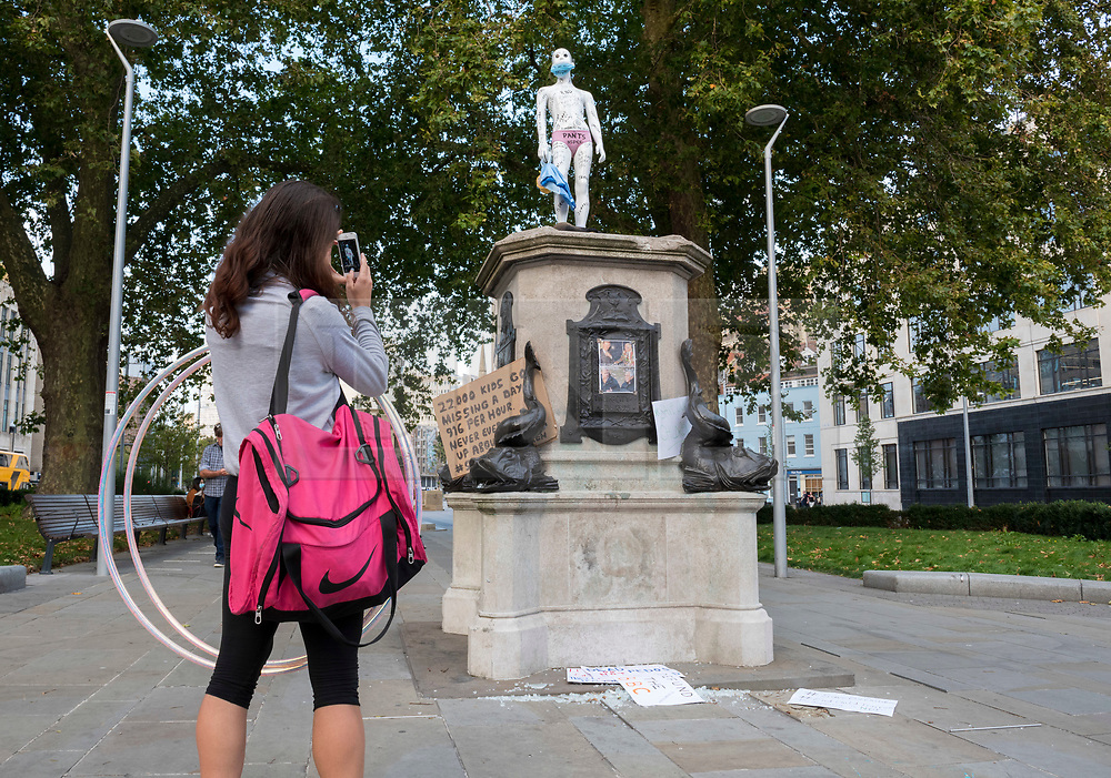 """© Licensed to London News Pictures; 19/09/2020; Bristol, UK. People view and photograph a new statue and placards against child exploitation and child sex trafficking which have been placed on the plinth from where the statue of slave trader Edward Colston was pulled down and thrown into Bristol docks on 07 June during an All Black Lives/Black Lives Matter protest in memory of George Floyd, a black man who was killed on May 25, 2020 in Minneapolis in the US by a white police officer, that made headlines around the world. The artist behind this new statue against child exploitation is not known. Since the Colston statue was pulled down various other statues and artworks have been placed on the empty plinth without permission from Bristol City council, including a statue """"A Surge of Power (Jen Reid) 2020"""" by sculptor Marc Quinn of protester Jen Reid who was at the previous protest on 07 June. Photo credit: Simon Chapman/LNP."""