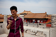 """Tourist watching his mobile phone inside  """"The Forbidden City"""" which was the Chinese imperial palace from the Ming Dynasty to the end of the Qing Dynasty. It is located in the middle of Beijing, China. Beijing is the capital of the People's Republic of China and one of the most populous cities in the world with a population of 19,612,368 as of 2010."""