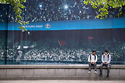 Two young men sit outside the Fan Zone, an enclosed area in Trafalgar Square for public-balloted ticket-holders during the Euro football tournament, on 8th July 2021, in London, England.