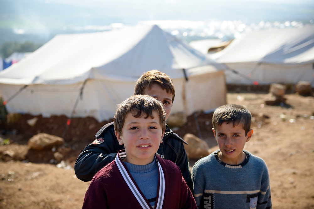 Three boys stand in front of tents at the camp for displaced persons in Atmeh, Syria.