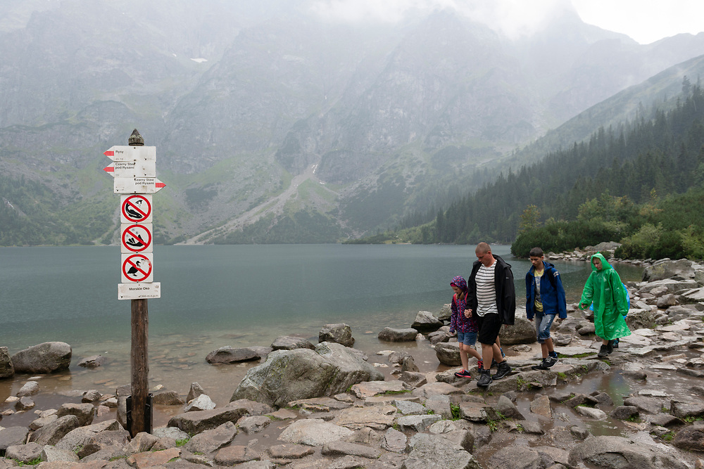 Morskie Oko, Poland - August 29, 2016: A family hikes at Morskie Oko, a famous lake in southern Poland. Located within Tatra National Park, Morskie Oko sits at an elevation of about 1400 meters above sea level.