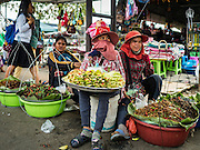 """15 FEBRUARY 2016 - ARANYAPRATHET, SA KAEO, THAILAND:  Cambodian snack vendors sit in the shade on the Thai side of the border in Aranyaprathet, Thailand. Thais selling bottled water in the border town of Aranyaprathet, opposite Poipet, Cambodia, have reported a surge in sales recently. Cambodian officials told their Thai counterparts that because of the 2016 drought, which is affecting Thailand and Cambodia, there have been spot shortages of drinking water near the Thai-Cambodian and that """"water shortages in Cambodia had prompted people to hoard drinking water from Thailand.""""    PHOTO BY JACK KURTZ"""