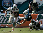 Miami Dolphins running back Ronnie Brown runs upfield as offensive lineman Jeno James wipes out Tennessee Titans defensive lineman Travis LaBoy during the Dolphins 13-10 victory over the Titans on September 24, 2005 at Dolphins Stadium in Miami, Florida.