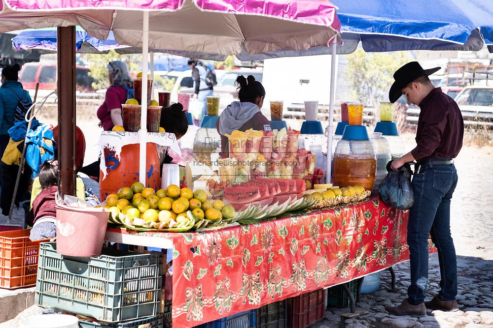 A Mexican cowboy buys fresh cut fruit at the Tuesday Market in San Miguel de Allende, Guanajuato, Mexico.