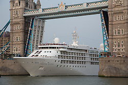 © Licensed to London News Pictures. 16/07/2013. London, UK. Silver Cloud, a huge luxury cruise ship arrives in London under Tower Bridge at 8.30pm on 16 July 2013 and passengers crowd the top deck of the ship during hot humid evening weather in the City of London. At 157 meters long, 22m wide and 16,800 tonnes, Silver Cloud is one of the largest ships to pass through Tower Bridge this year. Photo credit : Vickie Flores/LNP