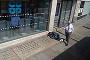 A wealthier man carrying his lunch, walks past a male lying on the pavement outside a branch of the Co-Op bank on the Strand, on 23rd June 2021, in Westminster, London, England.