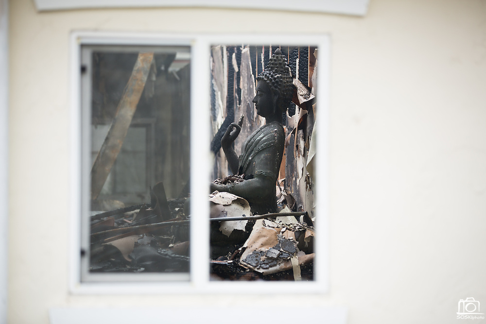 A Buddah statue sits with debris inside a home after the roof collapsed as multiple fire departments, including Milpitas Fire Department, Spring Valley Fire Department, and Cal Fire, work to contain and extinguish a structure fire at the 3000 block of Calaveras Road near Spring Valley Golf Course in Milpitas, California, on February 10, 2014. (Stan Olszewski/SOSKIphoto)