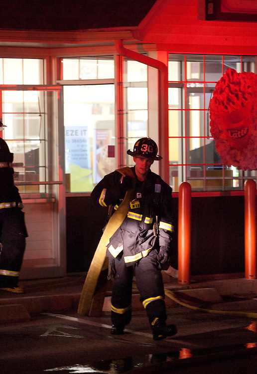 Boston, MA 5/26/11.A Boston Firefighter from Engine 30 carries a hose line out of the Dunkin Donuts at 1630 VFW Parkway early Thursday morning.  A fire started in the rear of the building but was quickly contained, officials said..Alex Jones / For The West Roxbury Transcript