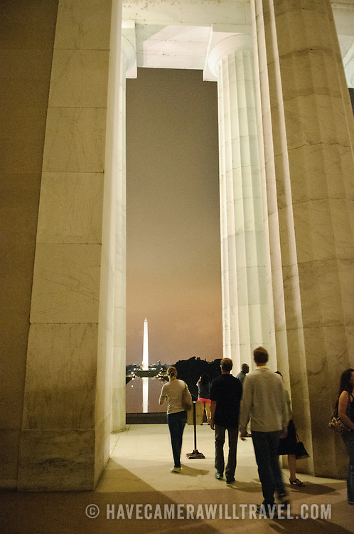Tourists visiting the Lincoln Memorial at night, with the Reflecting Pool, Washington Monument, and US Capitol Dome in the distance.