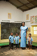 A teacher and school children in a classroom on a tea plantation in Munnar, a hill station in Kerala, India