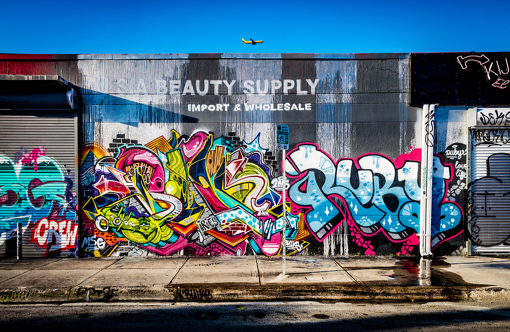 On final approach, an inbound jetliner glides over the graffiti-enhanced U.S.A. Beauty Supply warehouse in Miami's Wynwood District